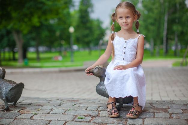 Śliczna dziewczyna siedzi na żelaznej figurze kaczki i dobrze się bawi