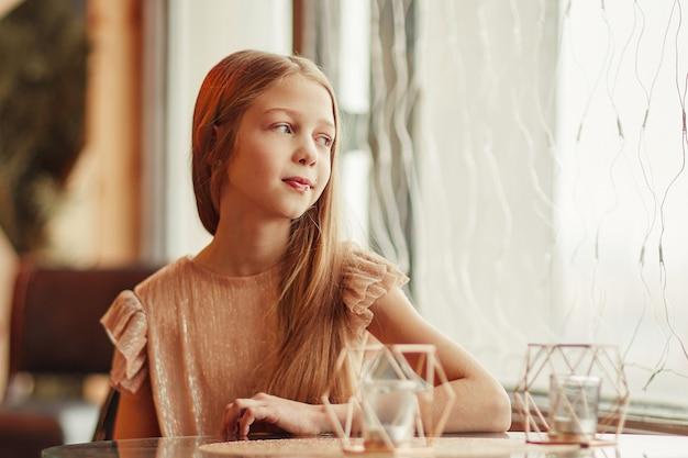 Śliczna dziewczyna siedzi przy stoliku w kawiarni