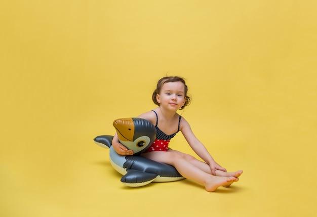 Śliczna dziewczyna siedzi w pływackim okręgu na żółtej przestrzeni. mała dziewczynka w stroju kąpielowym w kropki. koło do pływania w kształcie pingwina