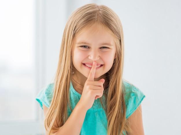 Śliczna dziewczyna śmiejąc się pokazując znak ciszy.