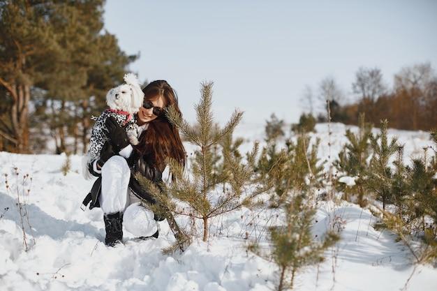 Śliczna dziewczyna spaceru w winter park. kobieta w brązowej kurtce. pani z psem.