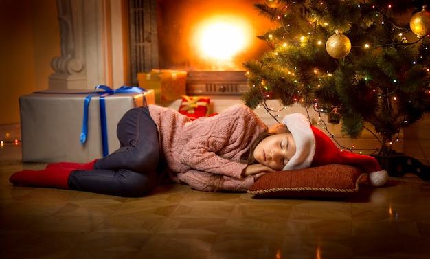 Śliczna dziewczyna śpi na podłodze pod choinką przy kominku