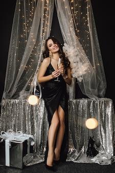Śliczna dziewczyna stoi obok dekoracji w srebrnym kolorze