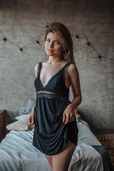 Śliczna dziewczyna stojąca przy łóżku w czarnej bieliźnie