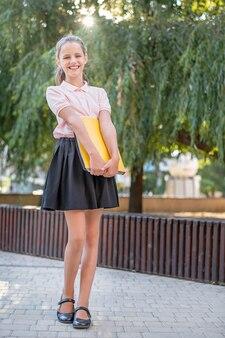 Śliczna dziewczyna studentka z uśmiechem żółtej folderu