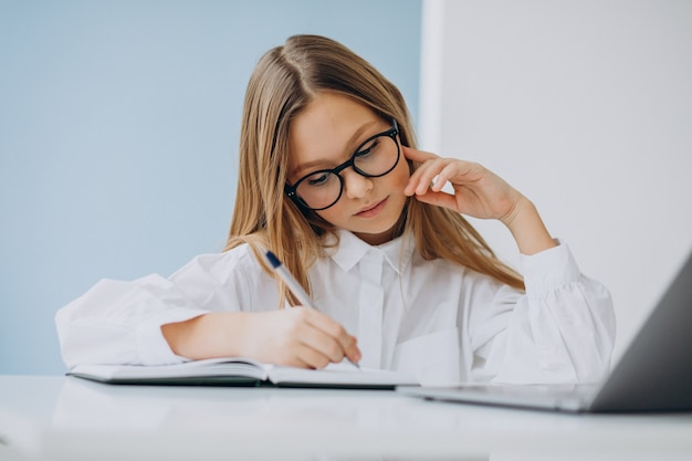 Śliczna dziewczyna studiuje na komputerze w domu