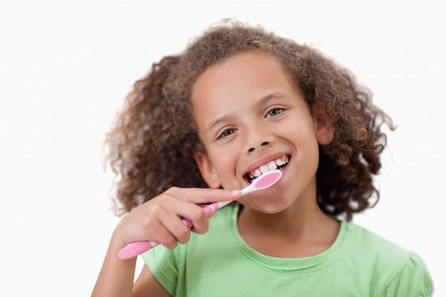 Śliczna dziewczyna szczotkuje jej zęby