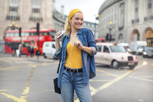 Śliczna dziewczyna tanczy podczas gdy słuchający muzyka, chodzi na ulicie
