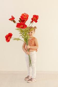Śliczna dziewczyna trzyma dużych czerwonych kwiaty