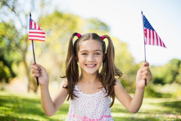 Śliczna dziewczyna trzyma flaga amerykańskie