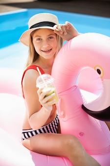 Śliczna dziewczyna trzyma smoothie z kapeluszem