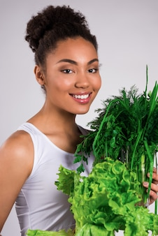 Śliczna dziewczyna trzyma w rękach bukiety zdrowego jedzenia.
