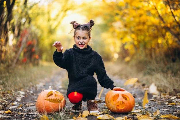 Śliczna dziewczyna ubierał w halloween kostiumu outdoors z baniami
