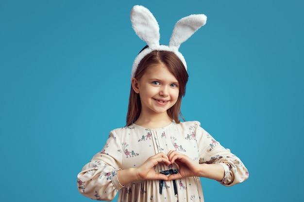 Śliczna dziewczyna ubrana w uszy królika sprawia, że gest serca na białym tle nad niebieską ścianą