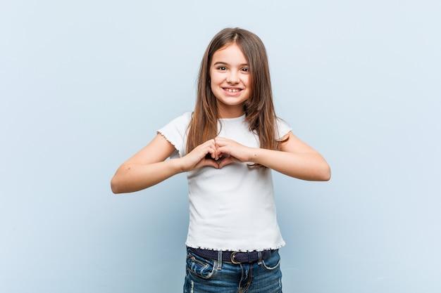 Śliczna dziewczyna uśmiecha się kierowego kształt z on i pokazuje ręki.