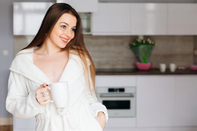 Śliczna dziewczyna w białym szlafroku stoi w nowoczesnej kuchni i trzyma filiżankę kawy lub herbaty. poranna kawa, koncepcja szczęścia.