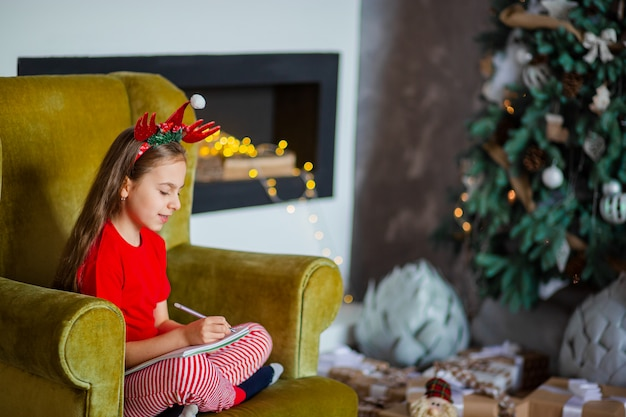 Śliczna dziewczyna w czapce mikołaja pisze list do świętego mikołaja w pobliżu choinki. szczęśliwe dzieciństwo, czas spełnienia pragnień.
