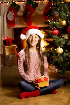 Śliczna dziewczyna w czapce mikołaja siedzi na podłodze z prezentem świątecznym przy kominku