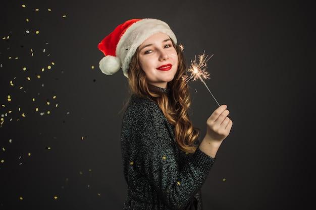 Śliczna dziewczyna w czapce świętego mikołaja raduje boże narodzenie i nowy rok na szaro. dziewczyna trzyma brylant, latające złote konfetti