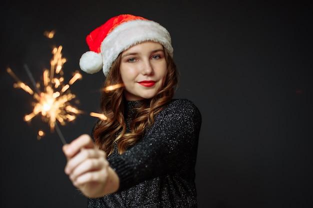 Śliczna dziewczyna w czapce świętego mikołaja raduje boże narodzenie i nowy rok na szaro. dziewczyna trzyma brylant