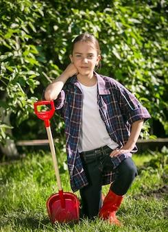 Śliczna dziewczyna w gumiakach pozuje z zabawkową łopatą w ogrodzie