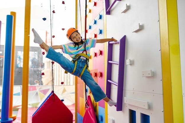 Śliczna dziewczyna w kasku wisi na ściance wspinaczkowej, centrum rozrywki, młody wspinacz. dzieci bawiące się, dzieciaki spędzają weekend na placu zabaw, szczęśliwe dzieciństwo