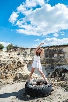 Śliczna dziewczyna w luźnym ubraniu spaceruje wśród piasków pustyni, lato idealny czas na wycieczkę