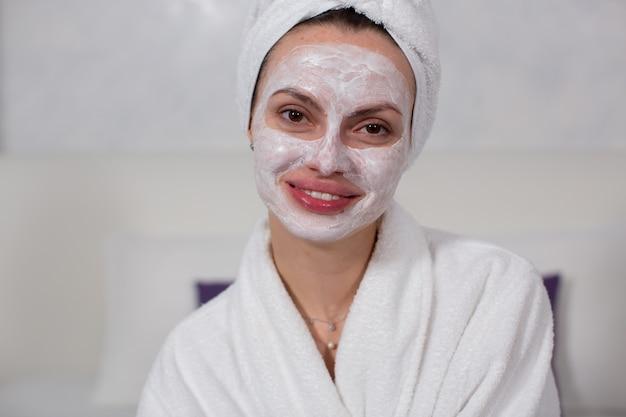 Śliczna dziewczyna w nawilżającej masce do twarzy, białej szacie i ręczniku na głowie, uśmiecha się i patrzy w kamerę zdjęcia zbliżeniowe dla salonów kosmetycznych wysokiej jakości zdjęcie