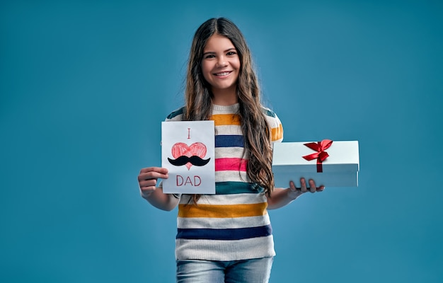 Śliczna dziewczyna w pasiastym, wielobarwnym swetrze trzyma pudełko i kartkę dla swojego taty na niebiesko.