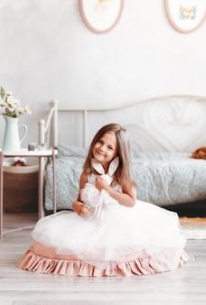 Śliczna dziewczyna w pięknej białej sukni siedzi z zabawką w jasnym pokoju. pionowy. szczęśliwe dzieciństwo