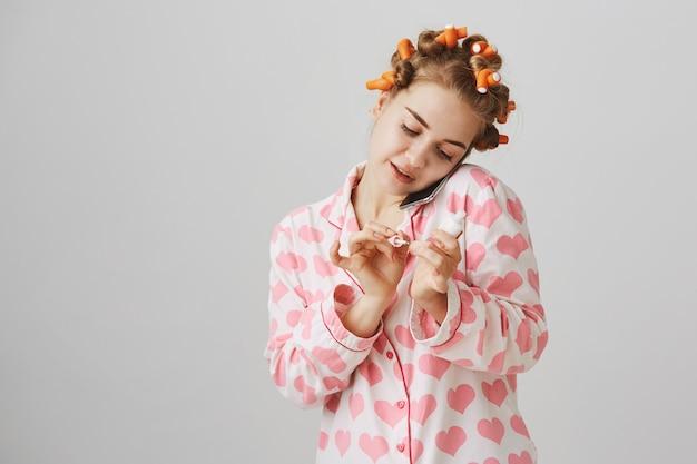 Śliczna dziewczyna w piżamie i lokówkach, rozmawia przez telefon podczas nakładania lakieru do paznokci
