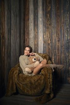 Śliczna dziewczyna w podkolanówkach i swetrze z misiem w rękach siedzi w fotelu w drewnianym pokoju.