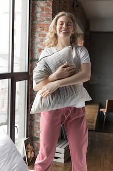 Śliczna dziewczyna w różowych piżamowych spodniach i białej koszulce stoi na łóżku z poduszką i uśmiecha się