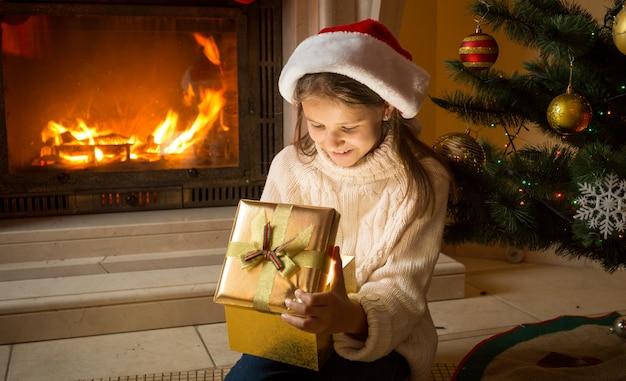 Śliczna dziewczyna w santa hat siedzi przy płonącym kominku i zagląda do świątecznego pudełka na prezent