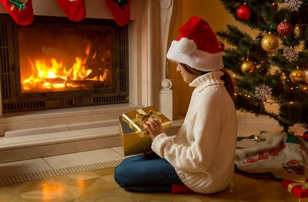 Śliczna dziewczyna w santa hat siedzi z świątecznym pudełkiem przy kominku i patrzy na ogień