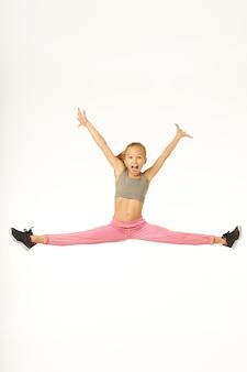 Śliczna dziewczyna w stroju sportowym podnosząca ręce i krzycząca z radości podczas skoku i wykonywania trików gimnastycznych. na białym tle