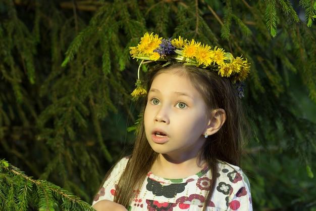 Śliczna dziewczyna w wieniec kwiatów patrzy z jodły w lesie. młoda wiedźma.