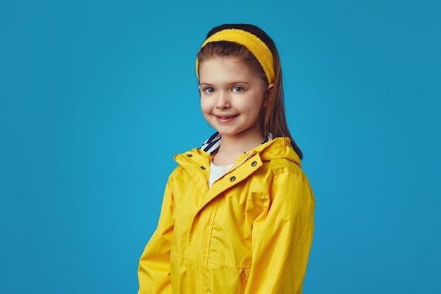 Śliczna dziewczyna w żółtym płaszczu przeciwdeszczowym z kapturem na niebieskiej ścianie ma dobry nastrój