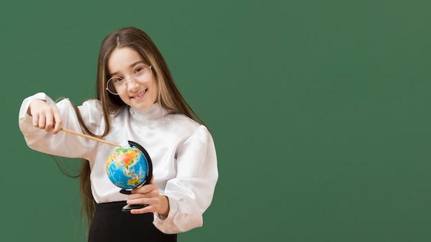 Śliczna dziewczyna wskazuje przy kulą ziemską