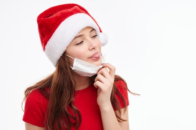Śliczna dziewczyna wystaje język maska medyczna czerwona koszulka świąteczna. wysokiej jakości zdjęcie