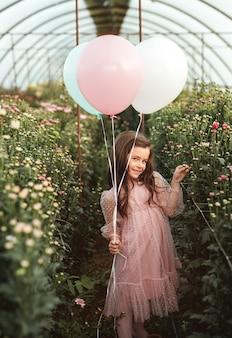 Śliczna dziewczyna z balonami w szklarni