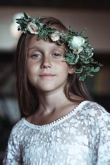 Śliczna dziewczyna z bardzo długimi włosami i pięknym wieńcem kwiatów na głowie