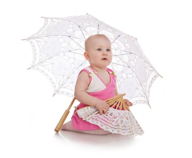 Śliczna dziewczyna z białym parasolem i zabawą na białym tle