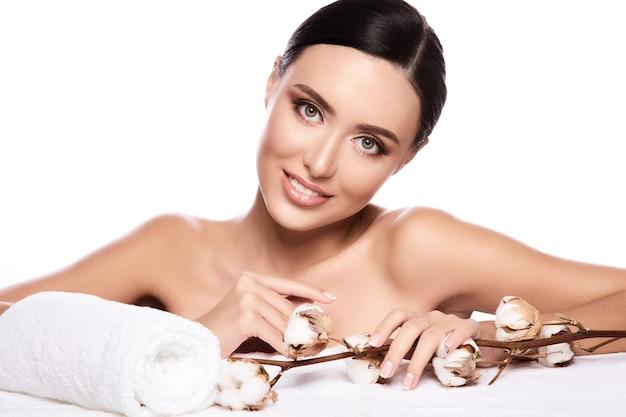 Śliczna dziewczyna z brązowymi włosami związanymi z tyłu, czystą, świeżą skórą, dużymi oczami i nagimi ramionami pozuje z kwiatem i ręcznikiem na białej ścianie, z bliska