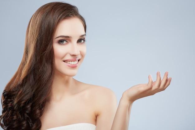 Śliczna dziewczyna z długimi brązowymi włosami, czystą świeżą skórą, dużymi oczami i nagimi ramionami, pozuje na szarym tle studia i trzyma rękę pokazującą produkt, patrząc na kamerę.