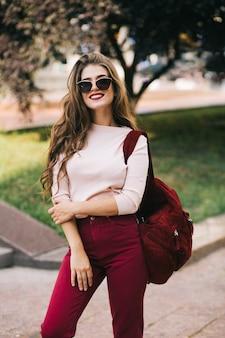 Śliczna dziewczyna z długimi włosami w okularach przeciwsłonecznych z workiem winnym i spodniami uśmiecha się w parku miejskim.