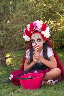 Śliczna dziewczyna z farbą na twarzy i dużym lizakiem w rękach siedzi na zielonej trawie pod drzewem jodłowym przed kamerą i delektuje się słodkimi smakołykami