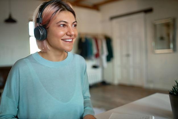 Śliczna dziewczyna z kolczykiem w nosie i różowawymi włosami siedzi przy biurku w bezprzewodowych słuchawkach, prowadzi lekcje głosowe przy użyciu czatu wideo z kamery internetowej, uczy się online, ma podekscytowany wesoły wygląd. ludzie i technologia