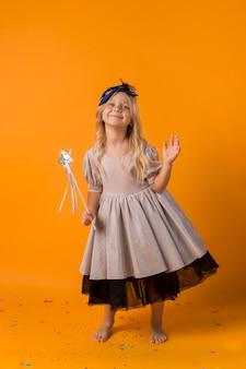 Śliczna dziewczyna z kostiumem i różdżką