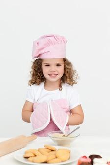 Śliczna dziewczyna z kuchennymi rękawiczkami podczas gdy przygotowywający ciastka